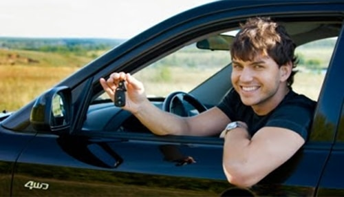 happy young man holding a car key sitting inside the car